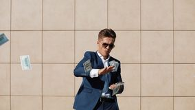 Jeune dispersion heureuse d'homme d'affaires les dollars et la danse drôle dans la rue Il marchant près du centre de bureau, lent banque de vidéos