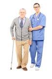 Jeune docteur aidant un monsieur plus âgé avec la béquille photographie stock