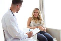 Jeune docteur attirant donnant un contrôle courant à la belle femme de pregnanat dans le bureau médical photo stock