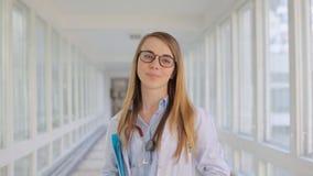 Jeune docteur avec du charme de femme souriant à l'appareil-photo dans l'intérieur banque de vidéos