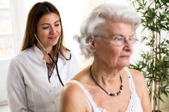 Jeune docteur avec la femme d'aîné d'examen de stéthoscope Photos stock