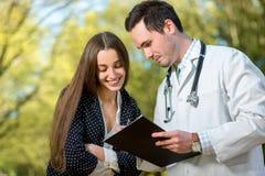 Jeune docteur avec la jeune et jolie patiente de femme images stock