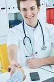 Jeune docteur caucasien masculin serrant la main au patient au bureau moderne lumineux de médecins dans l'hôpital image stock