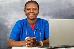 Jeune docteur de sourire s'asseyant au bureau photographie stock