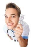 Jeune docteur drôle tenant des pilules image stock