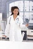 Jeune docteur ethnique dans le sourire de la chambre du docteur Photographie stock
