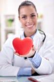 Jeune docteur féminin amical tenant un coeur dans des ses mains Images stock