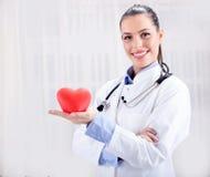 Jeune docteur féminin amical tenant un coeur dans des ses mains Photo stock
