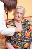 Jeune docteur féminin contrôlant le battement de coeur patient Image libre de droits