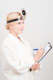 Jeune docteur féminin de sourire prenant des notes Photographie stock