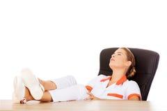 Jeune docteur féminin fatigué dormant avec des jambes sur le bureau Images libres de droits