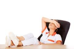 Jeune docteur féminin fatigué dormant avec des jambes sur le bureau Photos stock