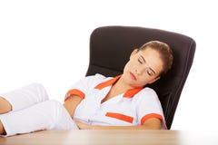 Jeune docteur féminin fatigué dormant avec des jambes sur le bureau Image stock