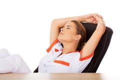 Jeune docteur féminin fatigué dormant avec des jambes sur le bureau Photographie stock libre de droits