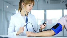 Jeune docteur féminin vérifiant la tension artérielle du patient dans la clinique photos stock