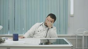Jeune docteur fatigué de travail, de regard à la montre et de boisson Images libres de droits