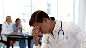 Jeune docteur inquiété tenant sa tête banque de vidéos