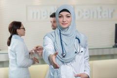Jeune docteur musulman féminin de sourire heureux donnant la main pour la poignée de main Images libres de droits