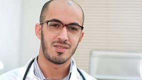 Jeune docteur parlant et regardant dans l'appareil-photo photographie stock libre de droits