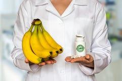 Jeune docteur tenant les bananes et la bouteille fraîches de pilules avec le vita Photos libres de droits