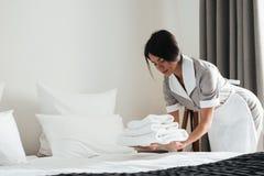 Jeune domestique d'hôtel mettant la pile de serviettes de bain blanches fraîches image stock