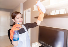 Jeune domestique nettoyant le miroir avec le jet à la maison, nettoyant le concept de service Photos libres de droits