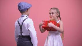 Jeune donner d'écolier a enveloppé actuel à la fille étonnée heureuse, célébration banque de vidéos