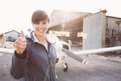 Jeune donner gai de pilote pouces  Image stock