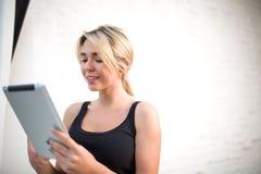 Jeune eBook avec du charme de lecture de femme sur le pavé tactile pendant le temps gratuit Images libres de droits