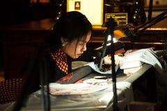Jeune embroideress asiatique travaillant dur sur une broderie faite main photo stock