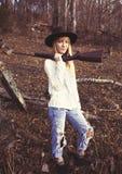 Jeune emplacement blond de femme dans les bois avec une arme à feu Photos libres de droits