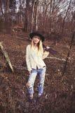 Jeune emplacement blond de femme dans les bois avec une arme à feu Photo stock