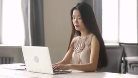 Jeune employé asiatique de femme d'affaires à l'aide de l'ordinateur portable sur le lieu de travail dans le bureau clips vidéos