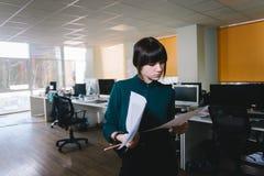 Jeune employé de bureau élégant avec une expression sérieuse examinant des documents d'entreprise Photo libre de droits