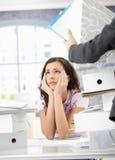 Jeune employé de bureau ayant excessif travail Photographie stock libre de droits
