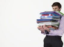 Jeune employé de bureau de sexe masculin portant les reliures lourdes photographie stock libre de droits