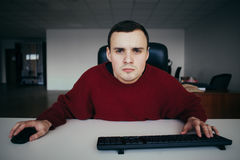 Jeune employé de bureau de sexe masculin regardant soigneusement votre moniteur d'ordinateur In camera vue intéressée photographie stock libre de droits