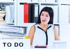 Jeune employé de bureau féminin choqué par le montant considérable d'écritures Concepts de date-butoir photo stock