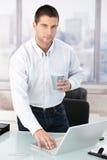 Jeune employé de bureau occasionnel à l'aide de l'ordinateur portatif dans le bureau Images libres de droits