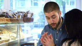 Jeune employé de magasin masculin aidant son client féminin choisissant la pâtisserie banque de vidéos