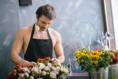 Jeune employé de magasin sélectionnant les meilleures fleurs à vendre Photos libres de droits
