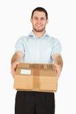 Jeune employé de sourire de poteau remettant le colis photographie stock