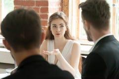 Jeune employé féminin partageant l'opinion avec des collègues au travail Photo libre de droits