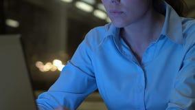 Jeune employé féminin travaillant sur le projet d'affaires la nuit dans le bureau, carrière clips vidéos