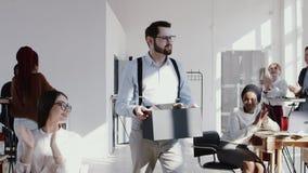 Jeune employé masculin caucasien heureux quittant le travail moderne de bureau avec une boîte, des applaudissements d'équipe et l clips vidéos