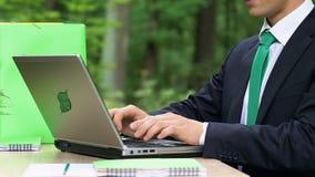Jeune employé masculin travaillant sur l'ordinateur portable qui respecte l'environnement, technologies d'économie de puissance clips vidéos