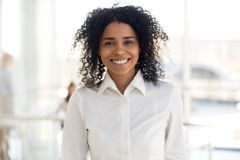 Jeune employée ou interne africaine de sourire dans le portrai de bureau images stock