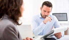 Jeune employeur attirant analysant le résumé de la femme Photo stock