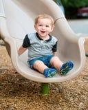 Jeune enfant de garçon d'enfant en bas âge jouant sur la glissière Photos stock