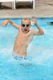 Jeune enfant de garçon sautant dans la piscine Image libre de droits